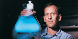 Man holding glowing blue flask.